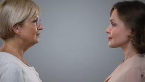 Ung kvinna och hög dam som ser sig grå bakgrund som åldras reflexion lager videofilmer