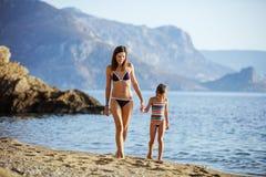 Ung kvinna och hennes dotter som promenerar stranden Royaltyfri Fotografi