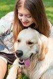 Ung kvinna och hennes hundgolden retriever i parkera på en sommardag Arkivbild