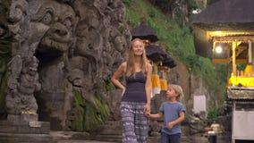Ung kvinna och hennes liten son som besöker elefantgrottan, Goa Gajah i den Ubud byn på den Bali ön arkivfilmer