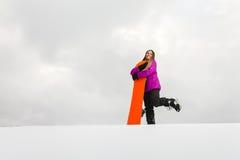 Ung kvinna och hennes orange snowboard Royaltyfri Bild