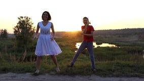 Ung kvinna och hennes sondansdisko lyckligt på en sjöbank på solnedgången i Slo-Mo stock video
