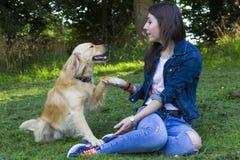 Ung kvinna och hund i skog Arkivbilder