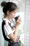 Ung kvinna och kaffekopp i hand Royaltyfri Foto