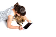 Ung kvinna och katt genom att använda minnestavladatoren på vit bakgrund Fotografering för Bildbyråer