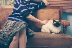 Ung kvinna och katt på soffan Royaltyfria Bilder