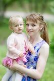 Ung kvinna och liten flicka i parkera arkivbild