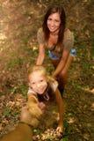 Ung kvinna och liten flicka i skogen arkivfoton
