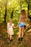 Ung kvinna och liten flicka i skogen arkivfoto