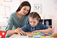 Ung kvinna och liten flicka med autistiskt spela för oordning royaltyfria foton