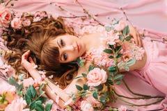 Ung kvinna och många blommor Arkivfoto