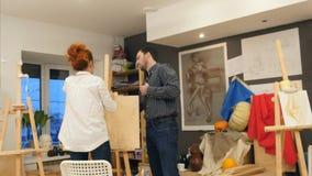 Ung kvinna och man som förbereder staffli för konstgrupp Royaltyfri Bild