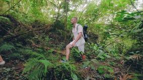 Ung kvinna och man som går på banan i tropisk djungelskog på sommardagen Lyckliga par som tillsammans in trekking lager videofilmer