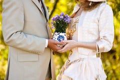 Ung kvinna och man som rymmer en bukett av blommor Arkivfoton