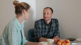Ung kvinna och man som talar, medan sitta i kök inomhus stock video