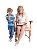 Ung kvinna och pojke som läser en bok. Arkivfoto