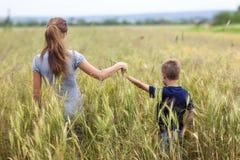 Ung kvinna och pys hennes sonanseende i vetefält uni Arkivbild