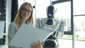 Ung kvinna och robot som i regeringsställning arbetar tillsammans arkivfilmer