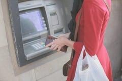 Ung kvinna på ATM Royaltyfri Bild