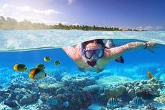 Ung kvinna på att snorkla i det tropiska vattnet arkivbilder