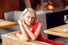 Ung kvinna på datum i restaurangen som sitter se ut drömma för fönster arkivfoton