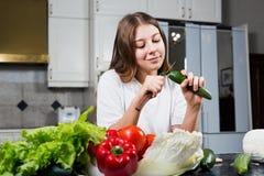 Ung kvinna på den bitande gurkan för kök Royaltyfria Bilder