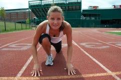 Ung kvinna på den startande linjen på Running spår Royaltyfria Foton