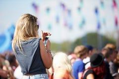 Ung kvinna på den utomhus- musikfestivalen genom att använda mobiltelefonen royaltyfri foto