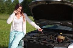 Ung kvinna på en bruten ner bil Royaltyfri Bild