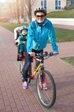 Ung kvinna på en cykel med den lilla sonen Arkivfoto