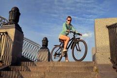 Ung kvinna på en cykel på stenmomenten mot den blåa himlen royaltyfria bilder