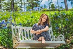 Ung kvinna på en gunga i en blommaträdgård Royaltyfria Bilder