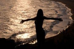 Ung kvinna på en kull vid havet i solnedgången Arkivbild