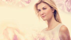 Ung kvinna på en rosa blom- bakgrund Royaltyfria Bilder