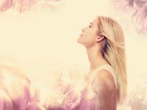 Ung kvinna på en rosa blom- bakgrund Arkivfoto