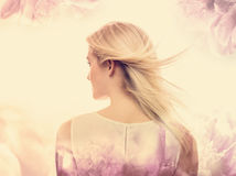 Ung kvinna på en rosa blom- bakgrund Arkivbilder