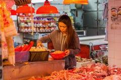 Ung kvinna på en shoppa i Kowloon, Hong Kong Royaltyfria Foton