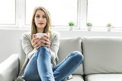 Ung kvinna på en soffa på vardagsrummet royaltyfri foto