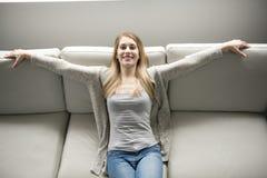 Ung kvinna på en soffa på vardagsrummet royaltyfria bilder