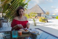 Ung kvinna på ferie i en tropisk ö som äter en sund frukost arkivfoto