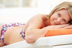 Ung kvinna på ferie som kopplar av vid simbassängen arkivfoton