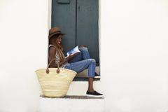 Ung kvinna på feriesammanträde på moment som läser en resehandbok royaltyfri foto