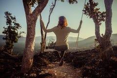 Ung kvinna på gunga i mountainden Royaltyfria Bilder