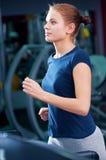 Ung kvinna på idrottshallen som körs på på en maskin Royaltyfri Foto