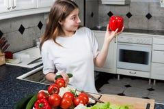 Ung kvinna på kök som ser röd peppar Arkivbilder