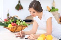 Ung kvinna på köket som gör online-shopping vid den minnestavladatoren och kreditkorten Arkivbilder