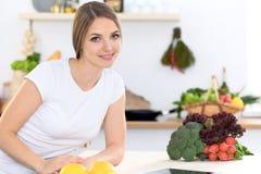 Ung kvinna på köket som gör online-shopping vid den minnestavladatoren och kreditkorten Arkivfoton
