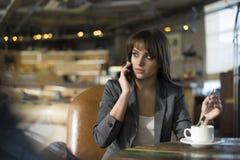 Ung kvinna på kafét som dricker kaffe och talar på mobiltelefonen Arkivbilder