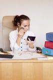 Ung kvinna på kontoret som retuscherar hennes smink Royaltyfria Foton
