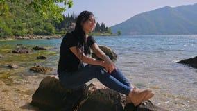 Ung kvinna på kusten som håller ögonen på havet lager videofilmer
